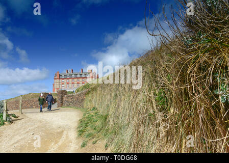 Two people walking along tThe coastal path near the Headland Hotel in Newquay in Cornwall. - Stock Image