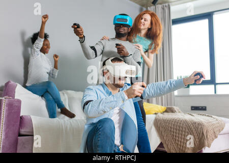 Multiethnic students in casual wear VR goggles using viewer for virtual reality game, while their diverse girlfriends having fun, laughing at them. Te - Stock Image