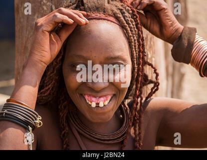 Africa, Namibia, Opuwo. Himba woman fixing her hair. Credit as: Wendy Kaveney / Jaynes Gallery / DanitaDelimont.com - Stock Image
