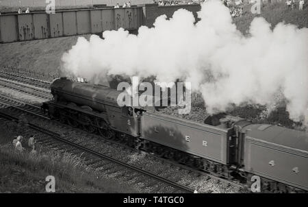 1969, historical, on the bride and grassbank, people watch as the iconic steam locomotive, The Flying Scotsman', goes past, England, UK. - Stock Image
