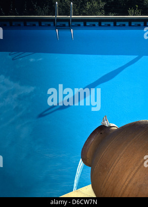 Swimming pool at French holiday village,with shadow of female about to dive into the pool,water flowing from pottery - Stock Image