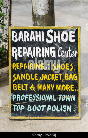 Hand painted ad for a shoe repair service in Pokhara, Nepal. - Stock Image