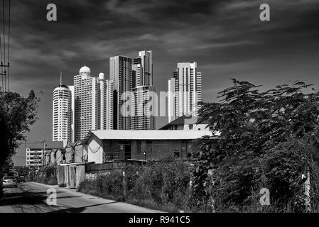 Lifestyle living contrast of High Rise modern apartment buildings against corrugated tin huts Black and white photography - Stock Image