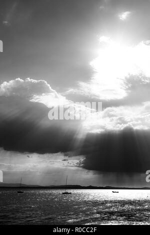 A couple of empty, little sailboat on a lake, beneath a moody sky with sun rays filtering through - Stock Image