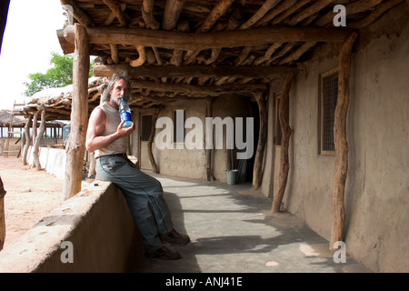 Tourist on the veranda of the lodge Wechiau Hippo Sanctuary northwestern Ghana Community Eco Tourism venture - Stock Image