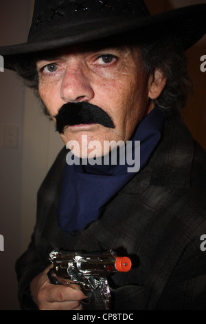A FIFTY YEAR OLD MAN DRESSED AS A COWBOY FOR A FANCY DRESS PARTY VERTICAL PLAIN BACKGROUND BDA - Stock Image