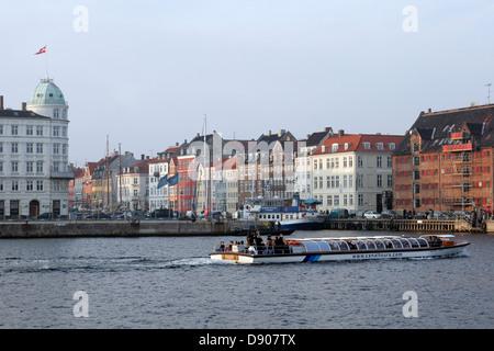 Tourist boat in front of the Nyhavn harbor, Copenhagen, Denmark - Stock Image