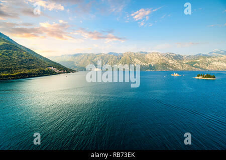 The sun sets on Ostrvo Sveti Đorđe, St. George Island, alongside Our Lady of the Rocks, two small islands off the coast of Perast in Bay of Kotor - Stock Image