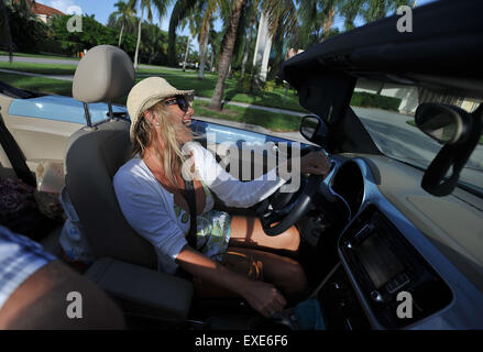 Woman enjoys singing in a convertable car in sun lifestyle - Stock Image