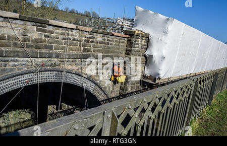 The old viaduct bridge at Millers Dale, Derbyshire in the Peak District being repaired with mortar by building engineers. - Stock Image