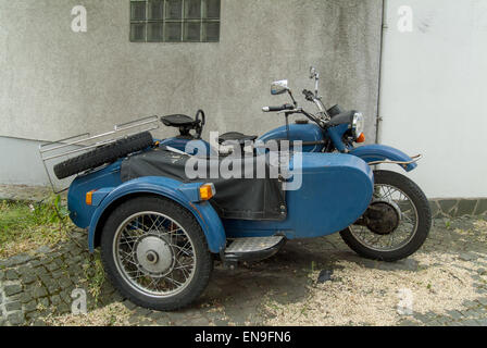 Old blue motorbike and sidecar in cobbled lane - Stock Image