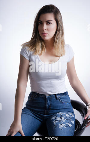 Girl with blonde brown hair in blue jeans sits on a bar stool and posing in studio. Woman portrait on white background and fashion concept. Close up - Stock Image
