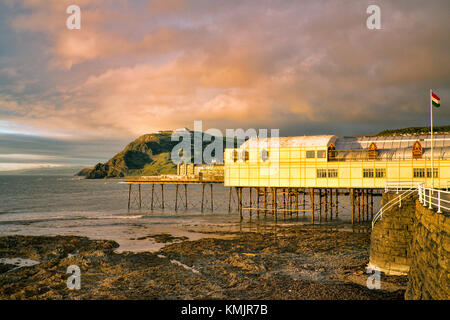 This stretch of welsh coast faces west, so gets some great sunsets. Aberystwyth pier opened in 1865, seven months - Stock Image