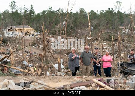 Opelika, Alabama, USA. 08th March, 2019. Residents stand amongst the destruction caused by a massive tornado as U.S. President Donald Trump visits the town March 8, 2019 in Beauregard, Alabama. The region was hit by a tornado on March 3rd killing 23 people. Credit: Planetpix/Alamy Live News - Stock Image