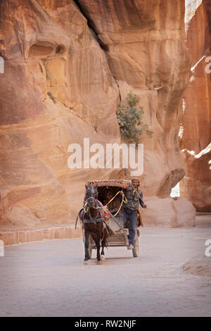 PETRA. A Jordanian horse and carriage taxi driver and his female passenger ride through the rocks from the Treasury building to the area exit. - Stock Image