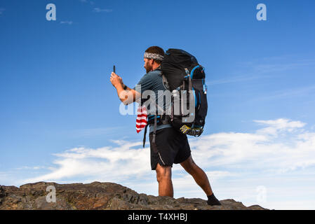 Male backpacker hiking on Appalachian Trail, taking photo with smart cell phone, Great Smoky Mountains National Park, outside Gatlinburg, TN, USA - Stock Image