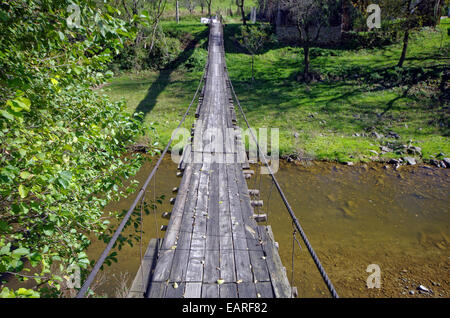 Small rope bridge over mountain river. Connection with the world. - Stock Image