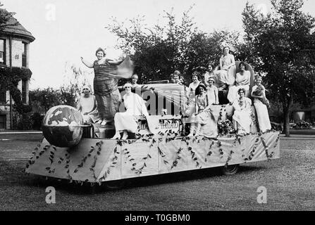 Young women pose atop a float after a Nebraska parade after winning the float contest, ca. 1925. - Stock Image