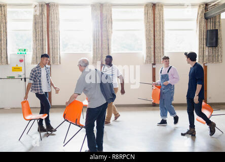 Men arranging chairs for group therapy in community center - Stock Image