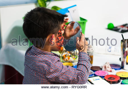 Poznan, Poland - March 2, 2019: Young boy watching his red painted face in a mirror during a birthday celebration party. - Stock Image