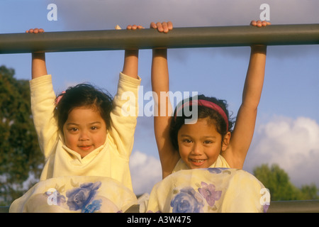 2 two Asian American sisters playing on fence rail - Stock Image