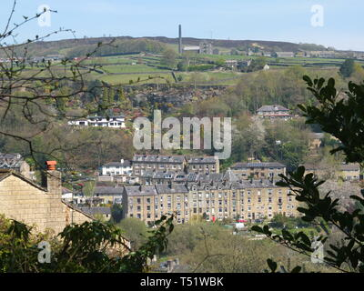 View of the terraces of the town of Hebden Bridge, Calderdale, West Yorkshire, UK and surrounding countryside through the trees from surrounding hills - Stock Image