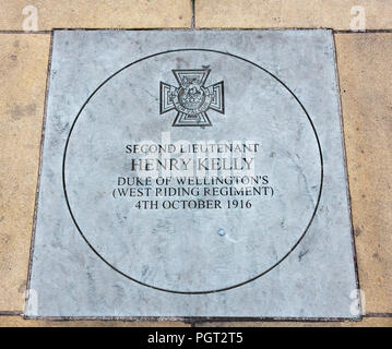 Plaque at foot of Manchester England war memorial showing Victoria Cross awarded Second Lieutenant Henry Kelly Duke of Wellington's (West Riding Regim - Stock Image
