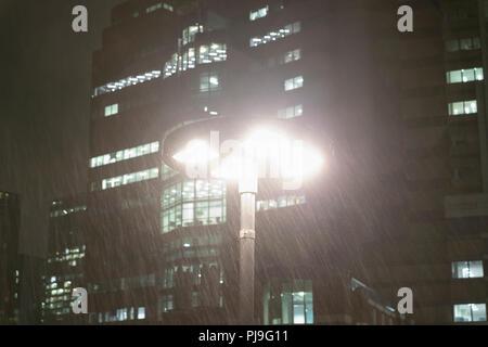 Rain falling around streetlamp below urban highrise buildings at night - Stock Image