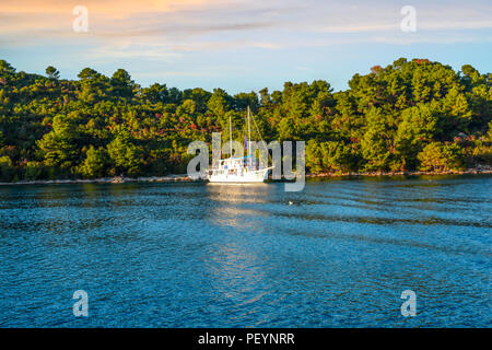 A sailboat yacht moors off on island near Hvar, Croatia on an autumn afternoon on the Dalmatian Coast. - Stock Image