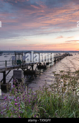 a wooden pier or jetty on the sea at sunrise - Stock Image