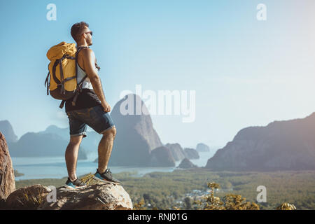Hiker stands on mountain or viewpoint and looks at view with sea and islands. Travel concept - Stock Image