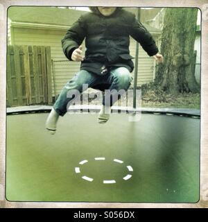 Young boy jumps on trampoline. - Stock Image