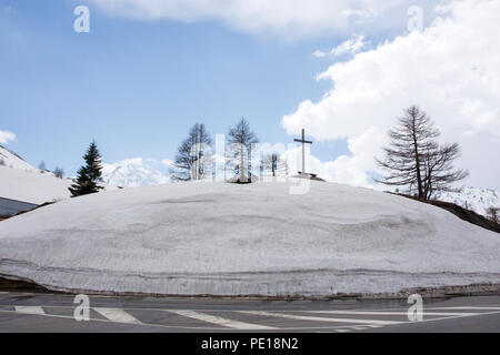 Snow covered hill with crucifix and pine trees at side of north approach to Simplon Pass on E62 Simplonstrasse road Switzerland in early May - Stock Image