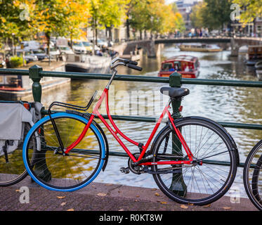 Amsterdam, red bicycle parked on the bridge - Stock Image