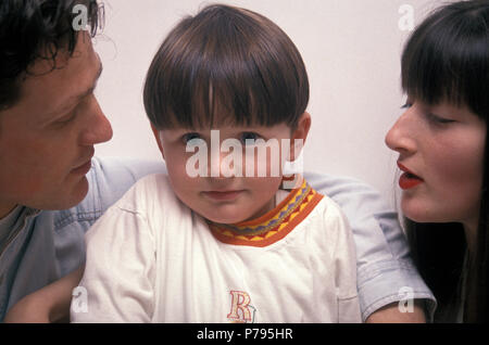 little blue eyed boy with freckles sitting between his parents looking into camera - Stock Image