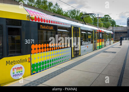 The Rainbow Tram, a Manchester Metrolink tram decorated with rainbow colours to celebrate the Manchester Pride festival, Manchester, England, UK - Stock Image