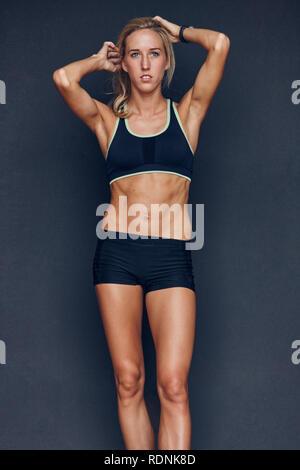 Portrait of female athlete on black background - Stock Image