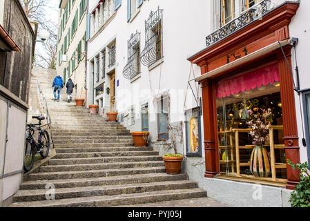 Zurich, Switzerland - March 2017: Couple walking in small medieval alley street in Zurich city centre, Switzerland - Stock Image