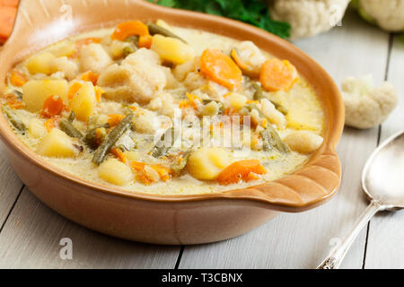 Vegetable soup with ingredients carrot, cauliflower, potato and parsley on rustic wooden table - Stock Image