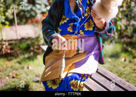 Midsection of woman spinning cotton while sitting on bench at yard - Stock Image