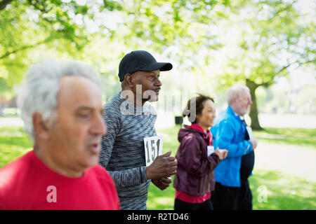 Active seniors running sports race in park - Stock Image