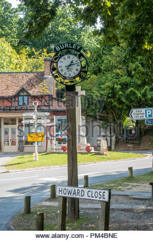 Village clock in the centre of Burley with a wrought iron surround depicting aspects of village life. - Stock Image