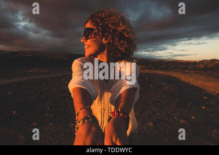 Cheerful happy people beautiful caucasian young woman turn fast and laugh a lot during dark evening sunset time - happiness and joyful emotions concep - Stock Image
