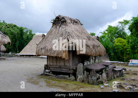 A 'bhaga' (small house representing female ancestors) & stone altar for rituals, Bena traditional village, Ngada District, Flores Island, Indonesia. - Stock Image