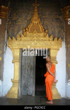 Buddhist monk in front of a door in Wat Xieng Thong in Luang Prabang , Laos - Stock Image