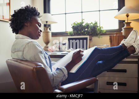 Businesswoman reviewing paperwork with feet up on desk - Stock Image