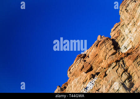 Orange colored rock wall in the desert under a bright blue sky. - Stock Image