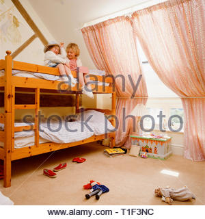 Sisters sitting on bunk bed in feminine bedroom - Stock Image