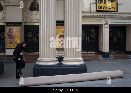 A young woman steps over a rolled-up carpet before fitters unroll and cut it for the interior of the Lyceum Theatre on Wellington Street, on 5th March 2019, in London, England. - Stock Image