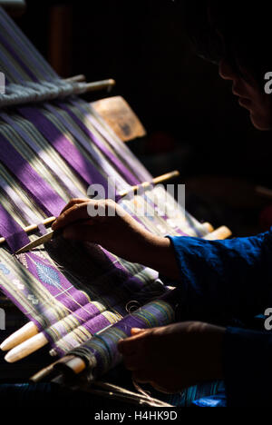Detail of woman's hand weaving traditional textile on back-strap loom in Thimphu, Bhutan - Stock Image